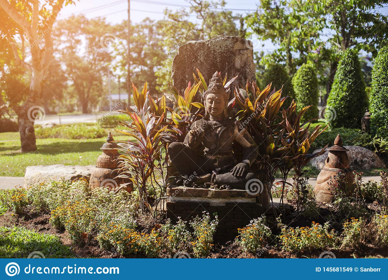 Thailand, Phuket. Buddha statue located on the street, surrounded by greenery. The concept of religion. The concept of tourism