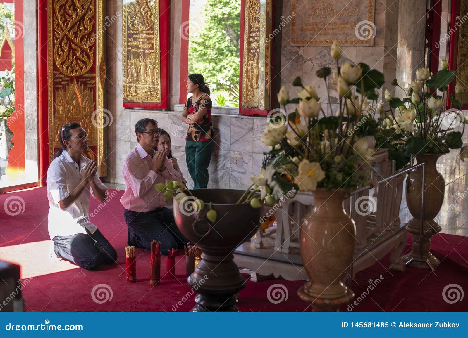 Thailand, Phuket, 01 18 2013 Ein Mann und seine Familie beten in einem buddhistischen Tempel morgens Das Konzept der Religion