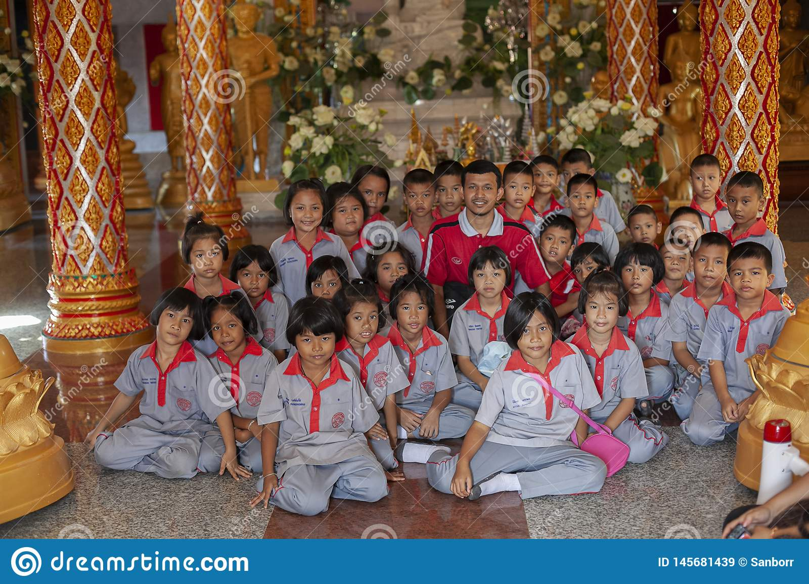 Thailand, Phuket, 01.18.2013. Elementary school students and a teacher in the Buddha temple, group photo. Education. Training.