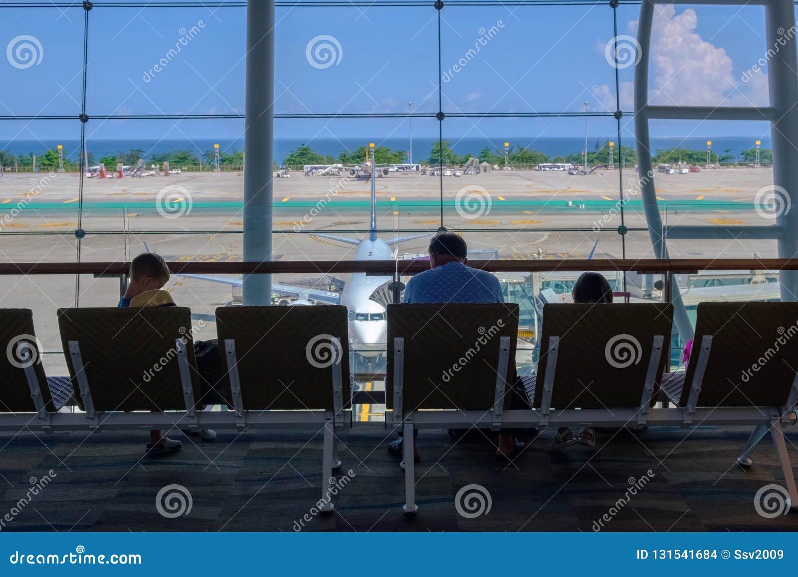 Thailand Phuket - 09 05 18 Familj, man och ungar som sitter och väntar tillsammans i flygplatsen för avvikelse