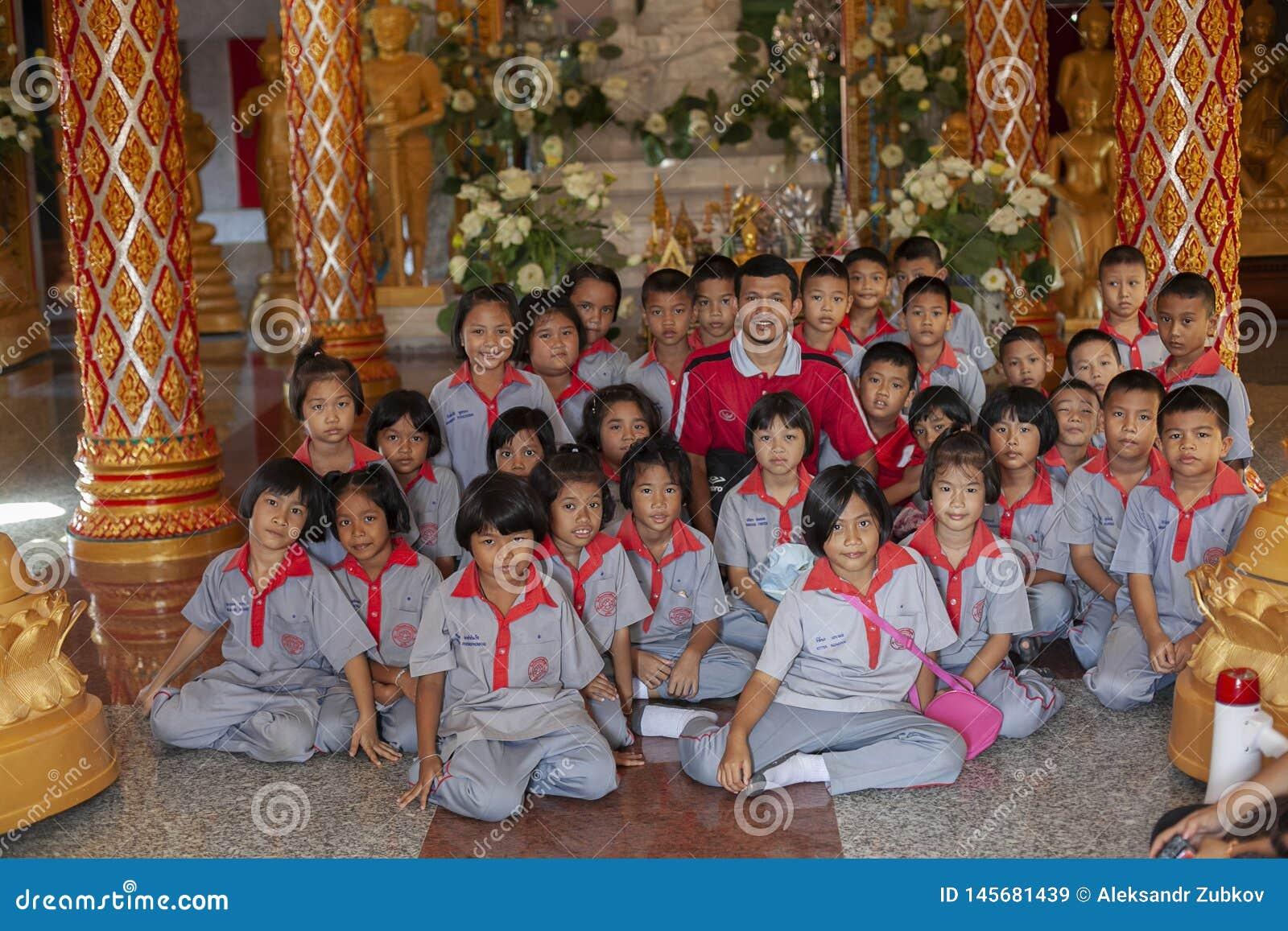 Thailand Phuket, 01 18 2013 Grundskolastudenter och en lärare i Buddhatemplet, gruppfoto Utbildning utbildning