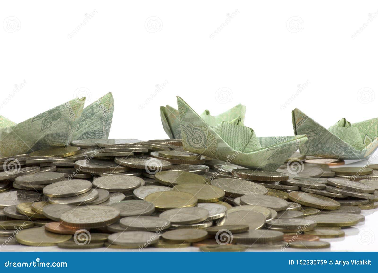 Thailand-W?hrungsm?nzen und -rechnung falteten zum Origami Segelboot auf wei?em Hintergrund mit cipping Weg