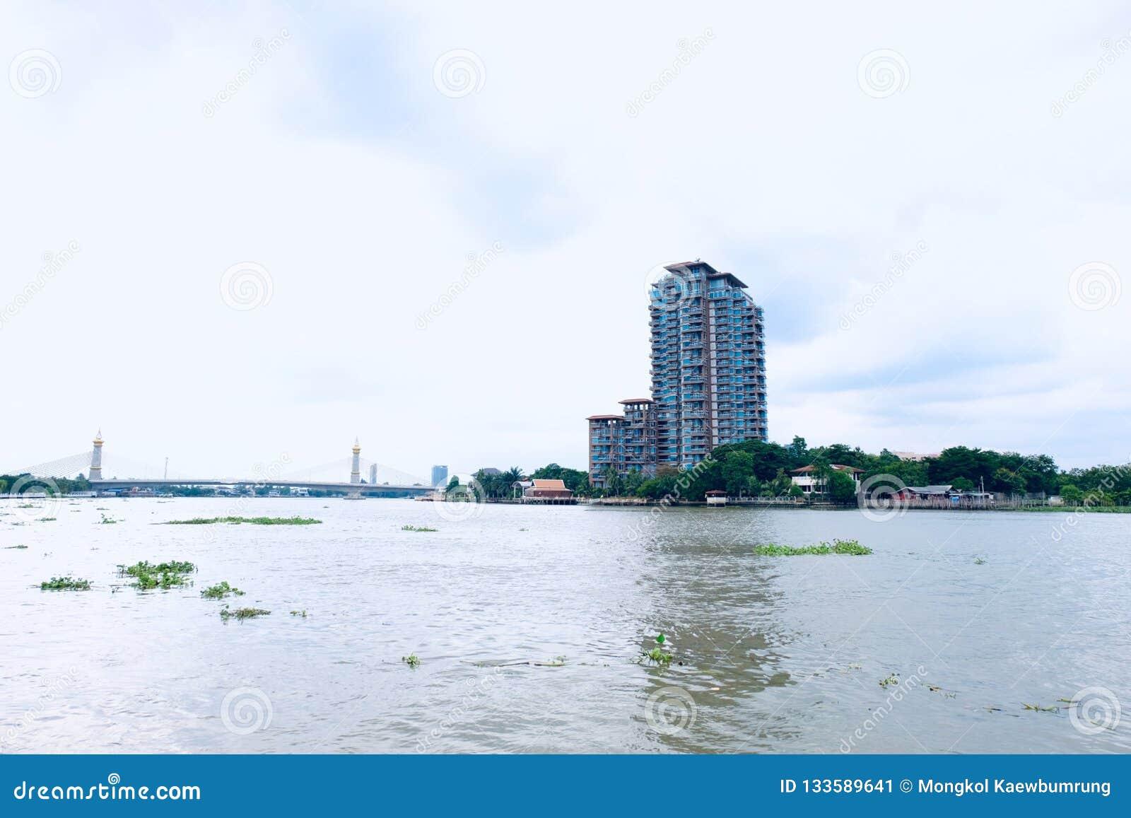 Thais Rivieroeverflatgebouw met koopflats achter de brug