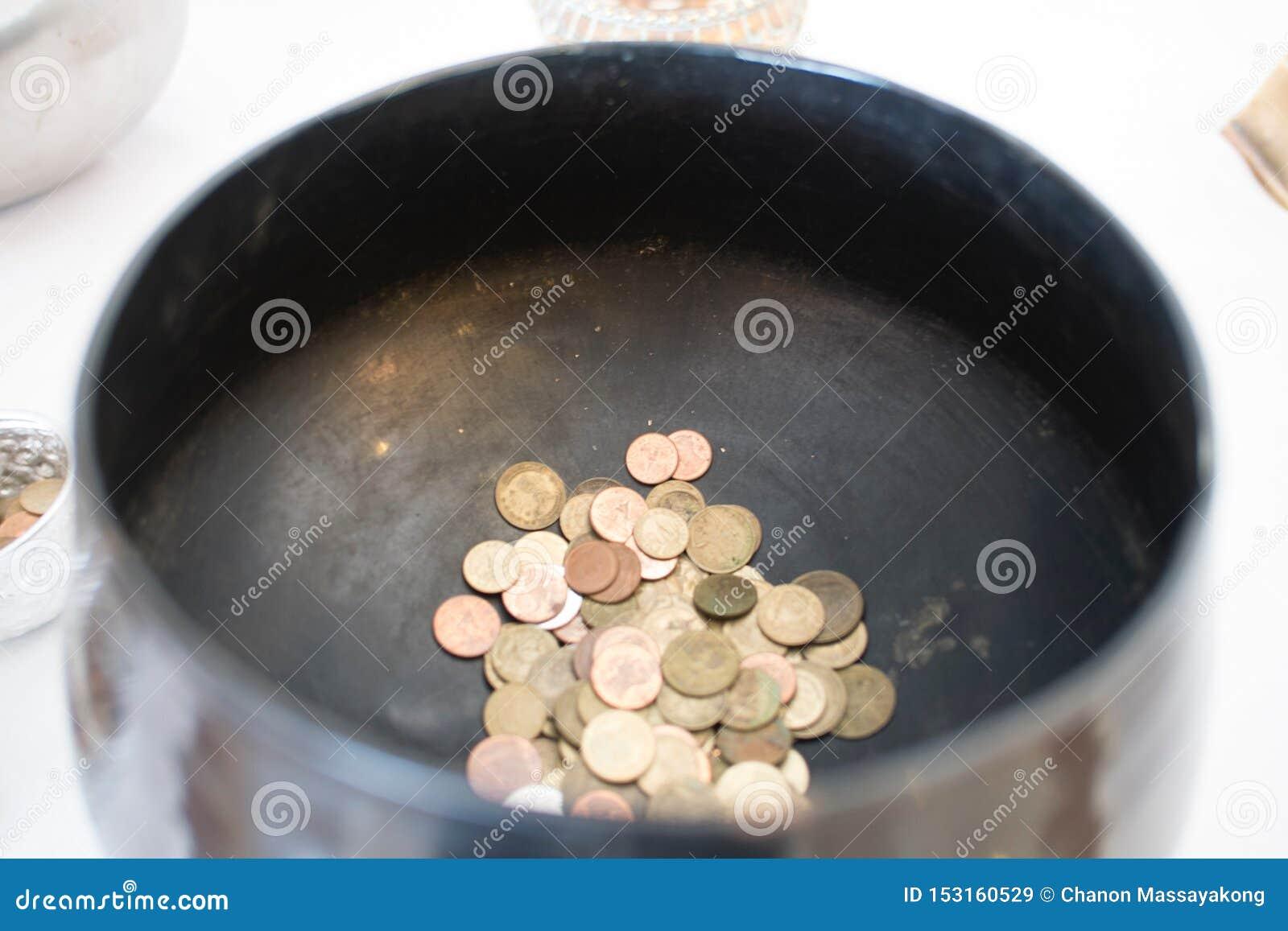 Thaise muntstukken in de kom van de monniksaalmoes