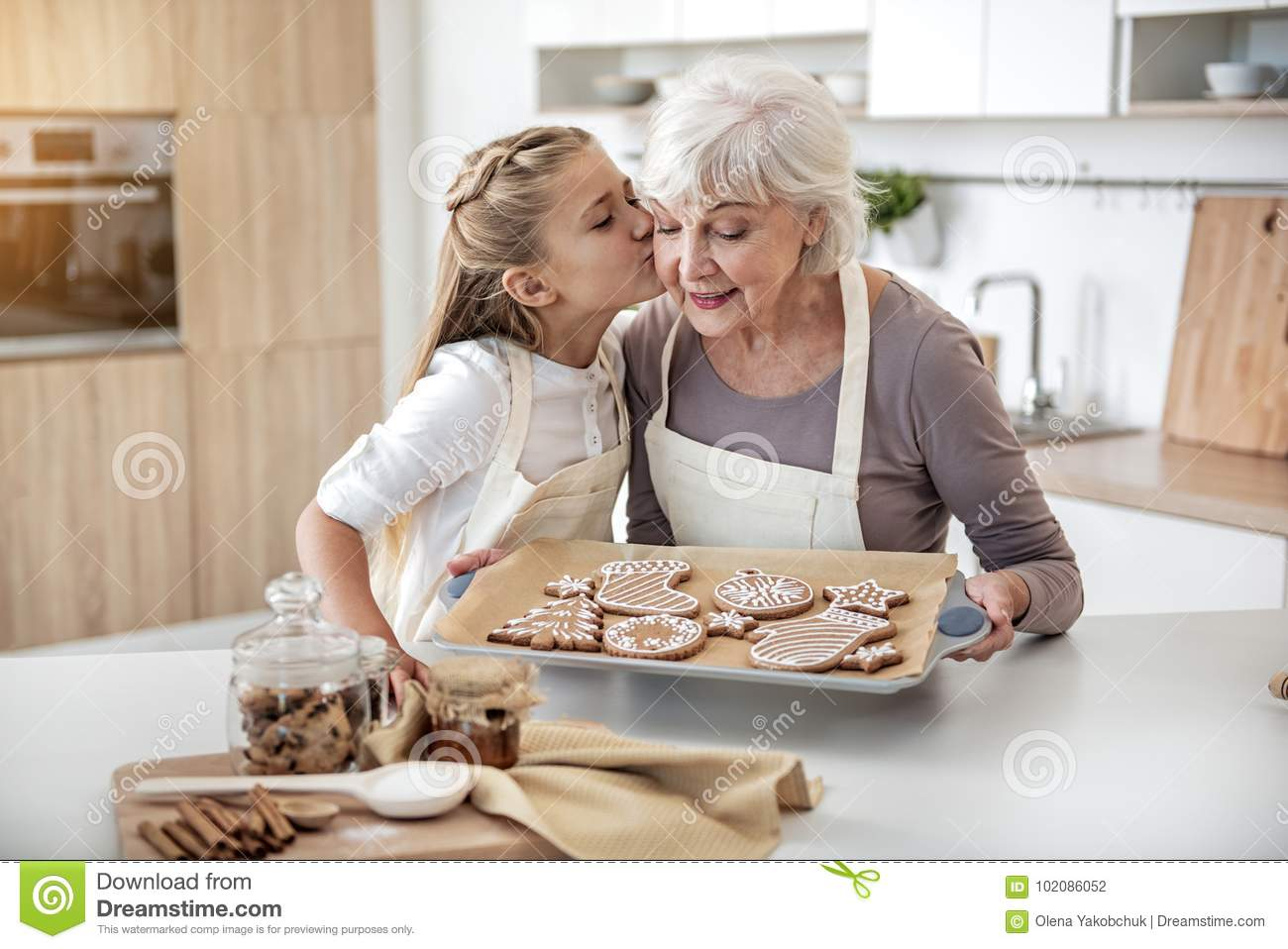 Happy child thanking grandma for sweet pastry