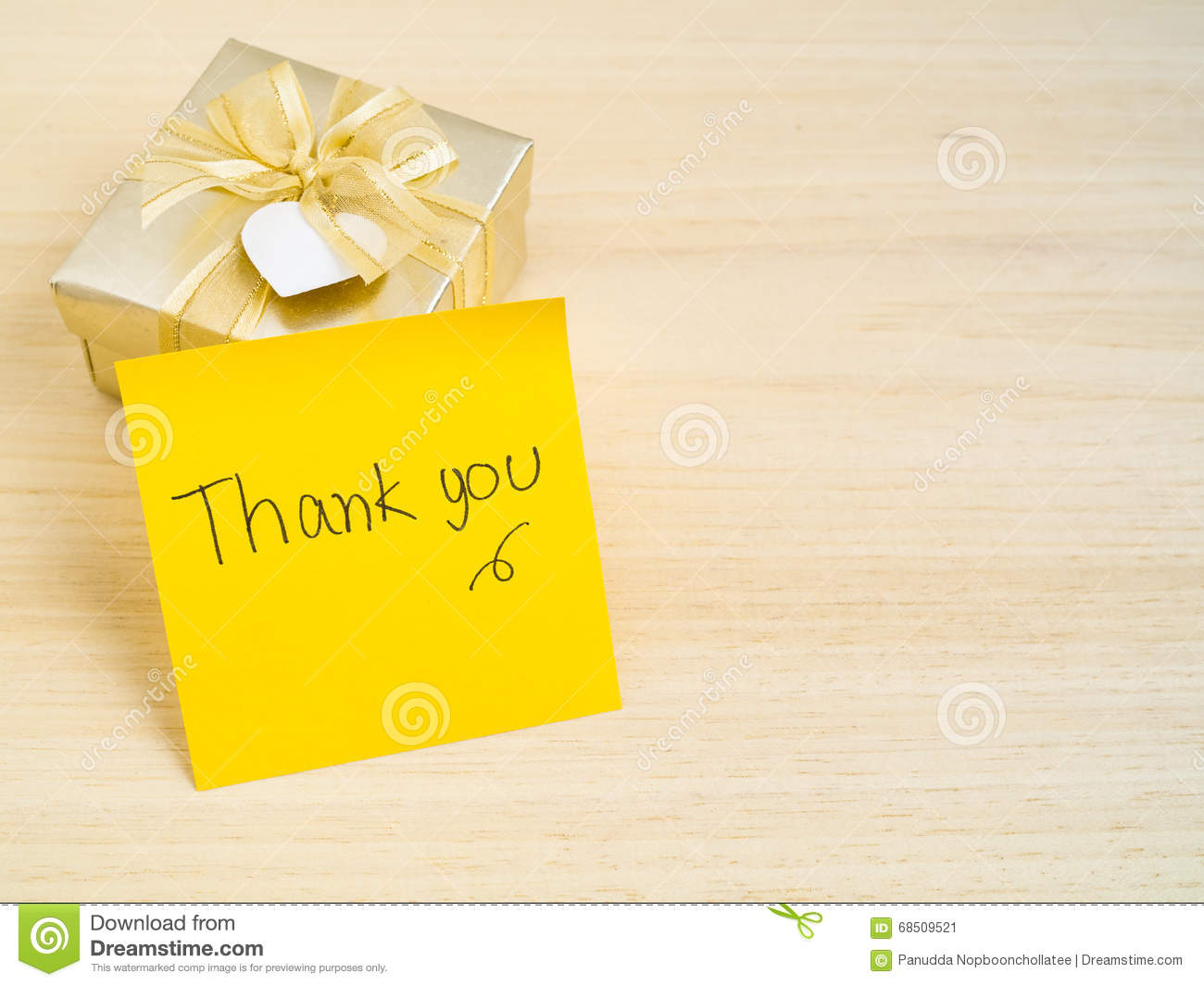 thank you words on sticky note with gold gift box on wood backgr