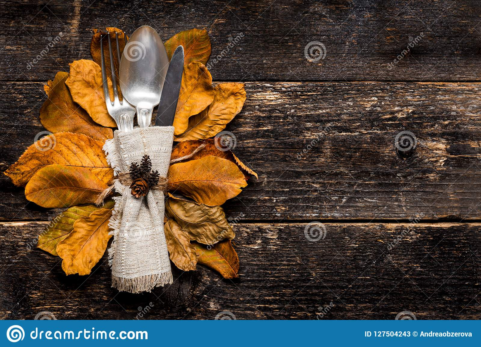 Thanksgiving Meal Setting. Seasonal table setting. Thanksgiving autumn place setting with cutlery and colorful fall fall leaves.