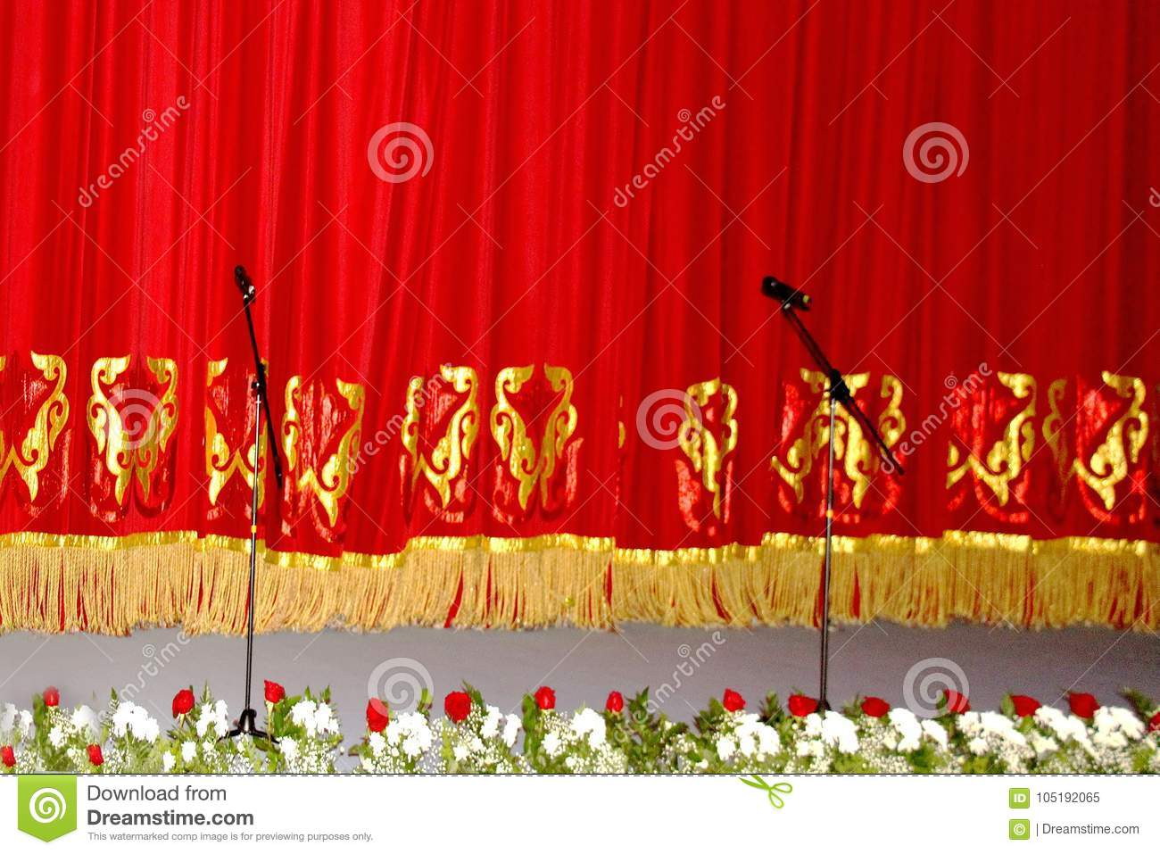 Theatrical red velvet curtain with gold pattern, and the microphones