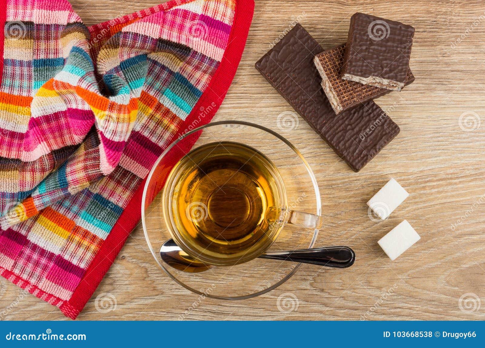 Thee, lepel, suiker, gebroken wafeltje in chocolade en servet