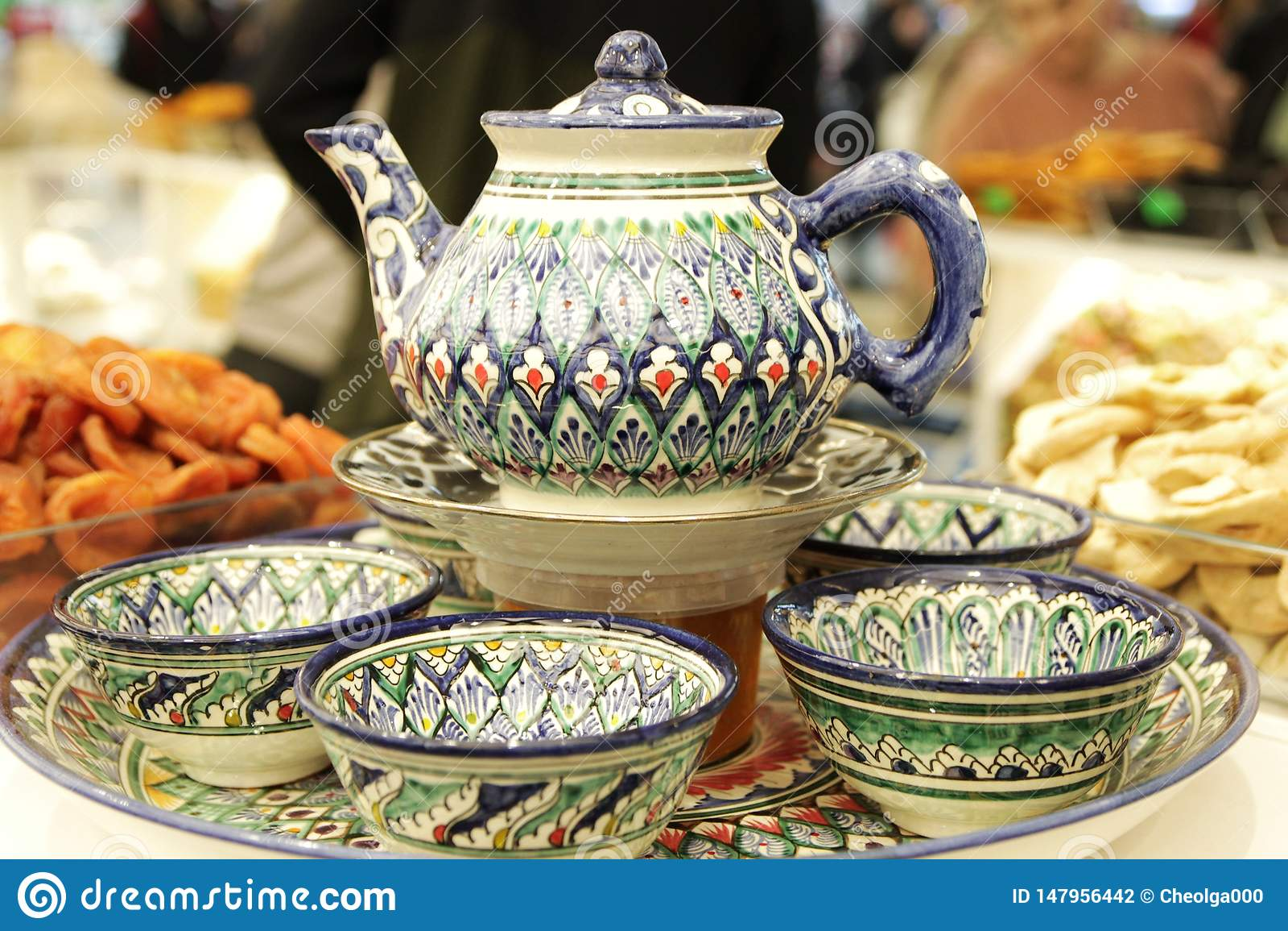 Theestel, theepot, koppen, geschilderde Turkse keramiek, snoepjes en droge vruchten