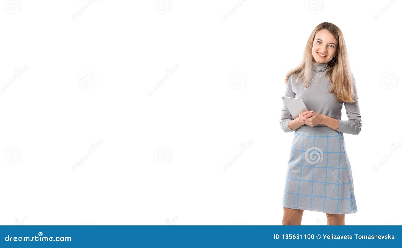 Thema bedrijfsvrouwentechnologie Mooie jonge Kaukasische blonde vrouw in het grijze kleding stellen die zich met tablethanden bev