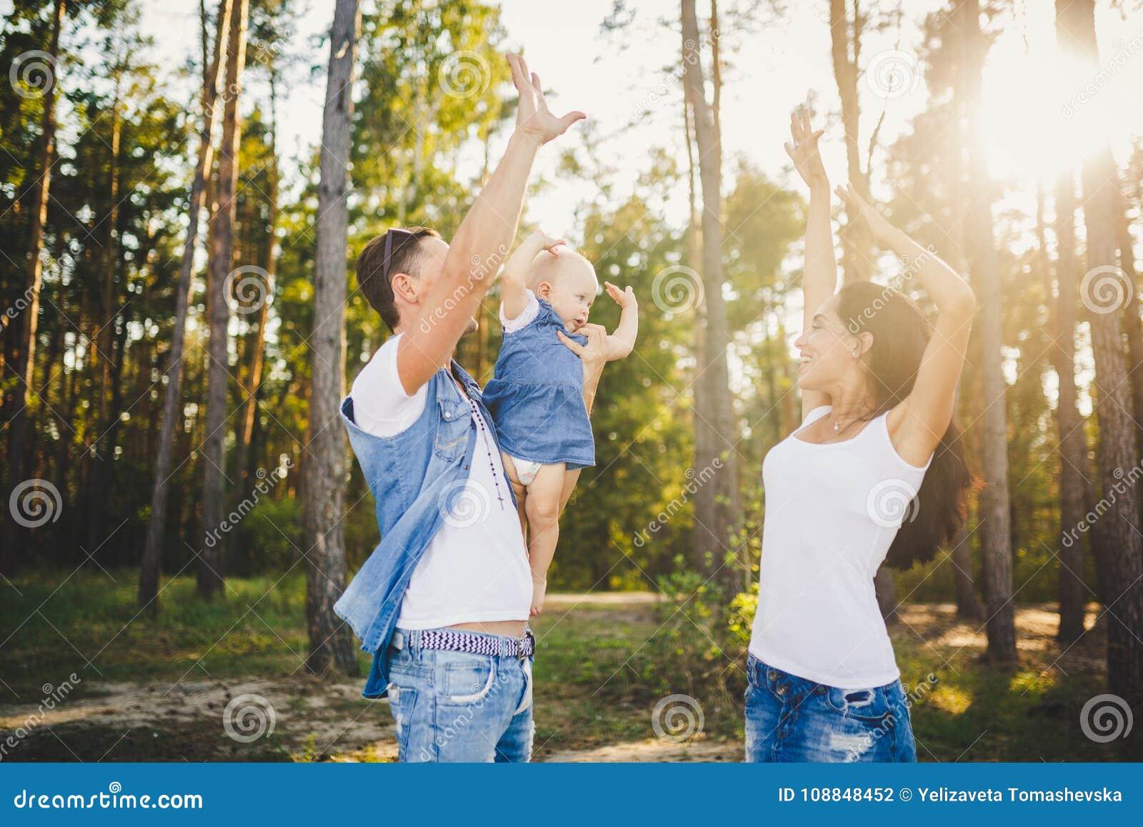 Themafamilienurlaub im kleinen Kind des Wald A hat Tochter mit Vati auf Schultern, hoben Mutterstände nahe bei ihr Arme an und