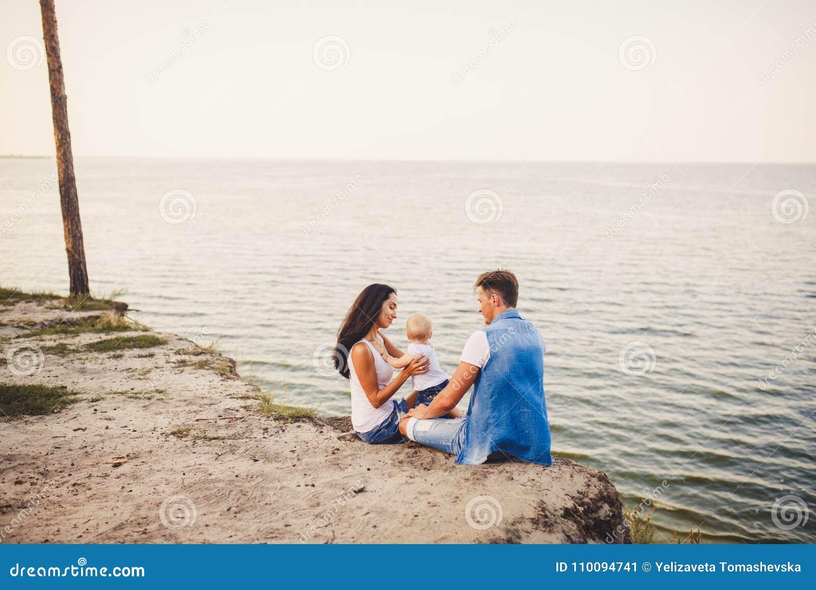 Themafamilienurlaub mit kleinem Kind auf der Natur und dem Meer Mutter, Vati und Tochter von einem Jahr sitzen in der Umarmung, M