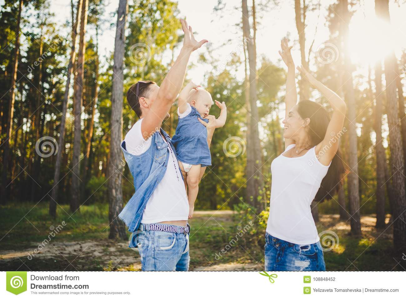 Theme family vacation in the forest. A small child has daughter with daddy on shoulders, mother stands next to her raised arms and