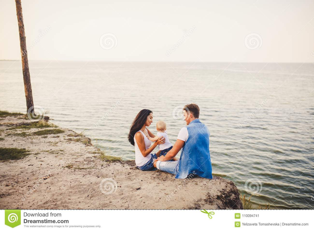 Theme family vacation with small child on the nature and sea. Mom, Dad and daughter of one year are sitting in embrace, girls in t