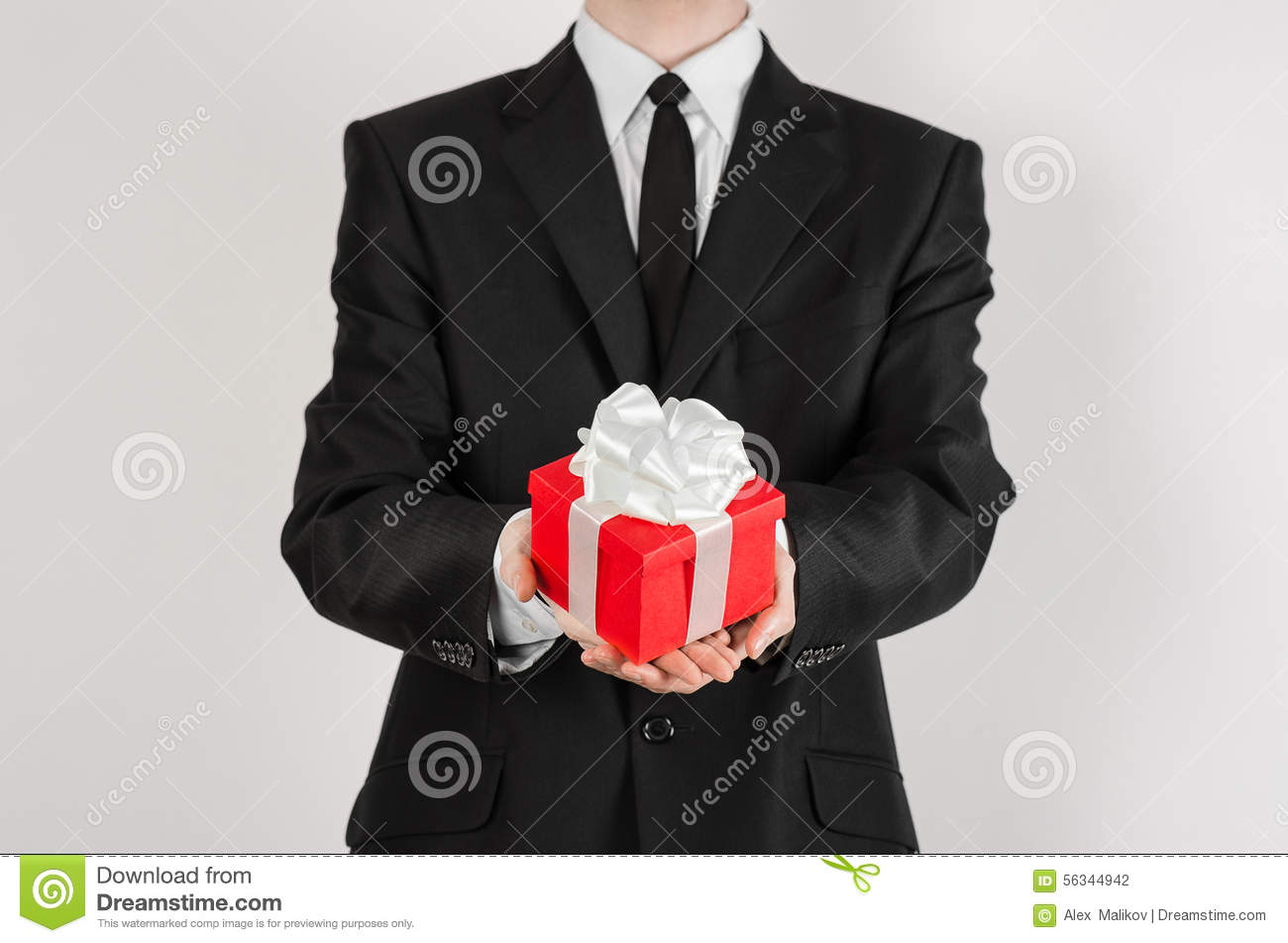 Theme holidays and gifts: a man in a black suit holds exclusive gift wrapped in red box with white ribbon and bow isolated on a