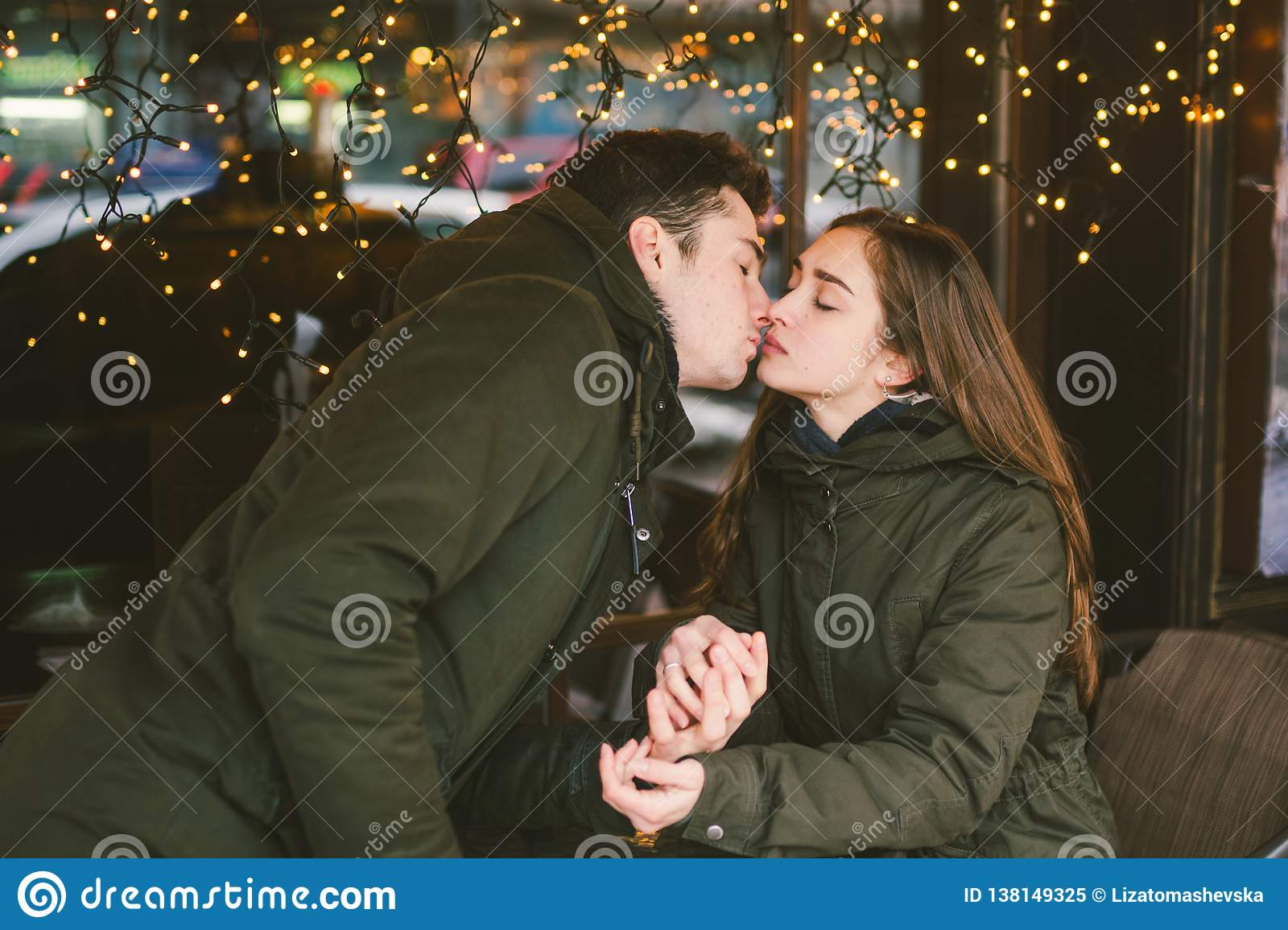 Theme love holiday Valentines Day. pair college students, Caucasian heterosexual lovers in winter, sit table of street