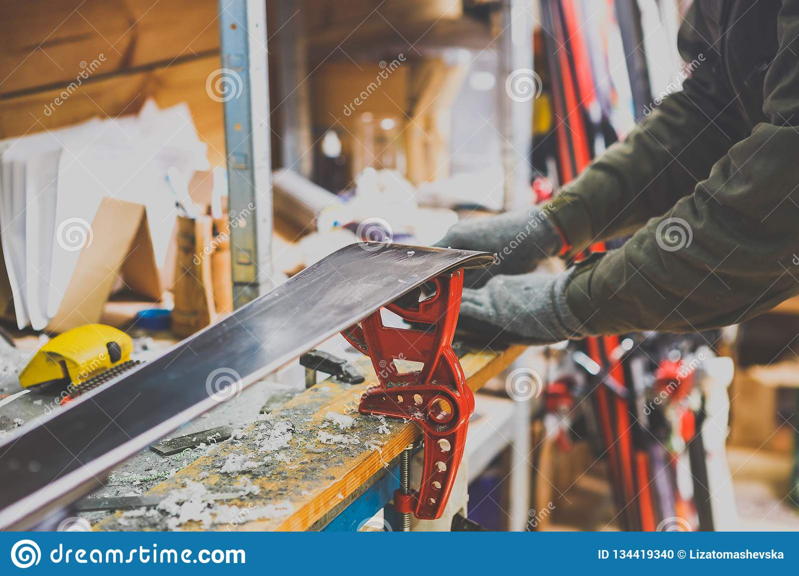 Theme repairs and maintenance of skis. The male worker is repairing work clothes, applying wax on the sliding surface onto skis