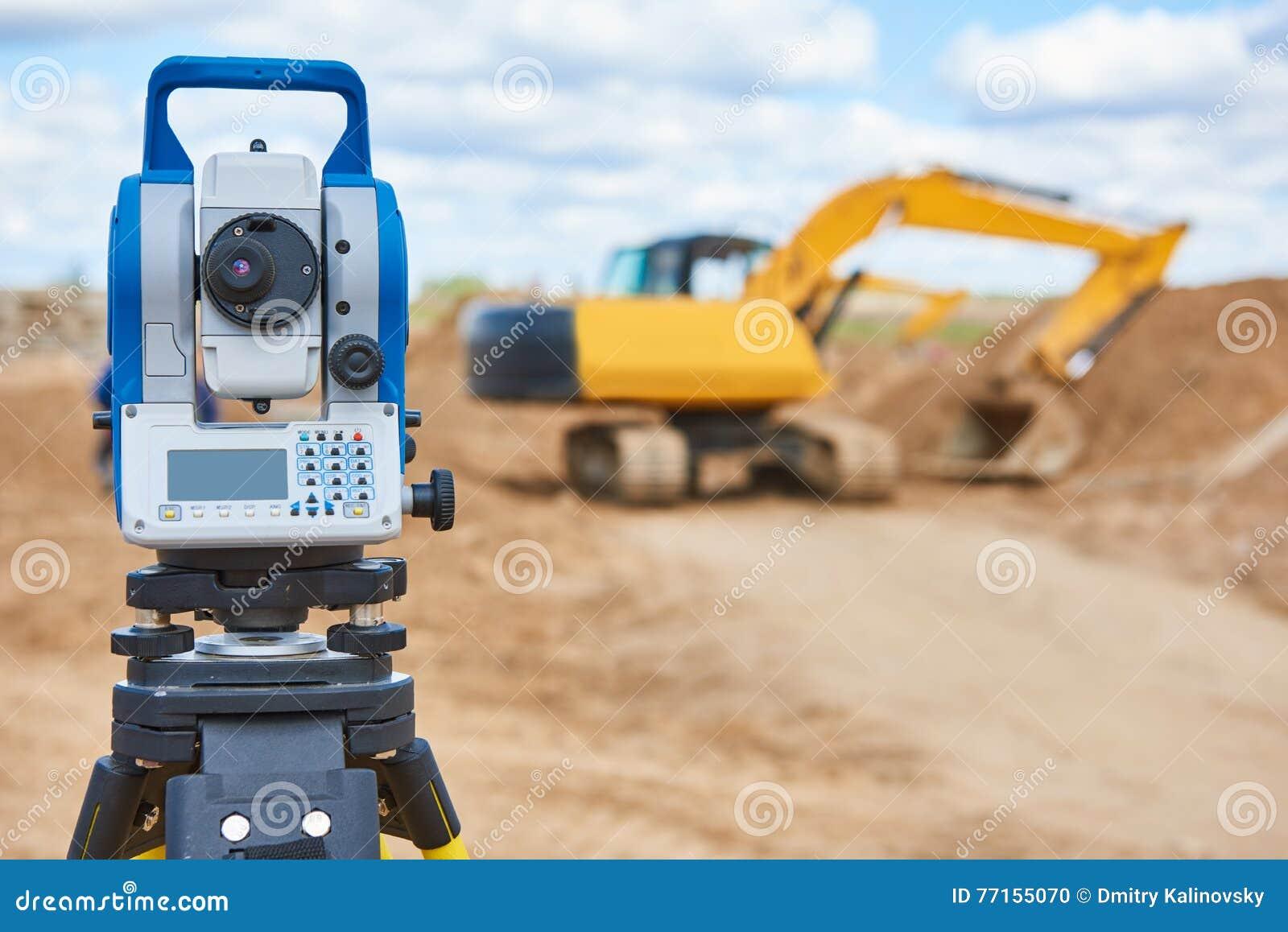 Theodolie d équipement d arpenteur au chantier de construction avec l excavatrice