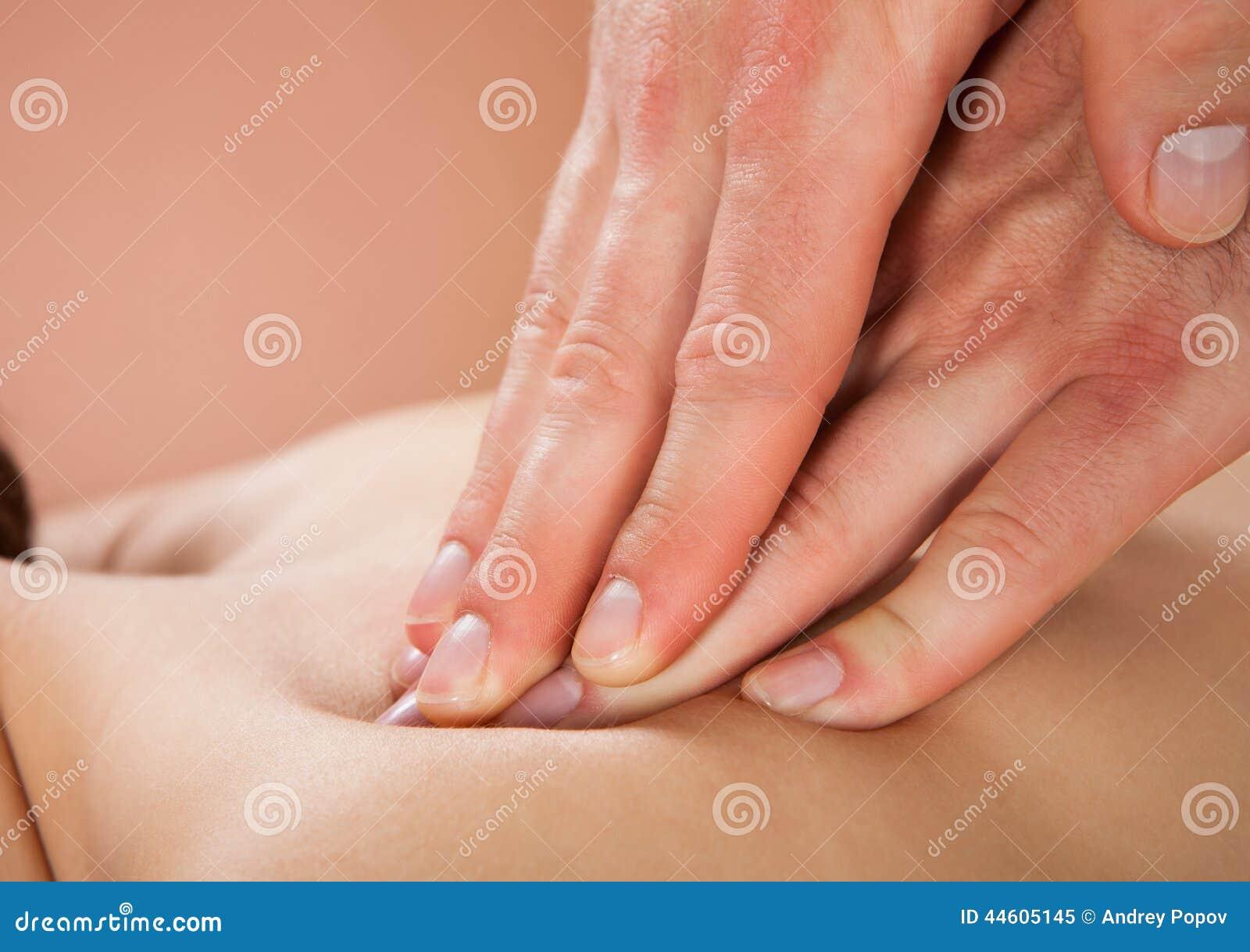 Therapeut, der die Rückseite des weiblichen Kunden am Badekurort massiert