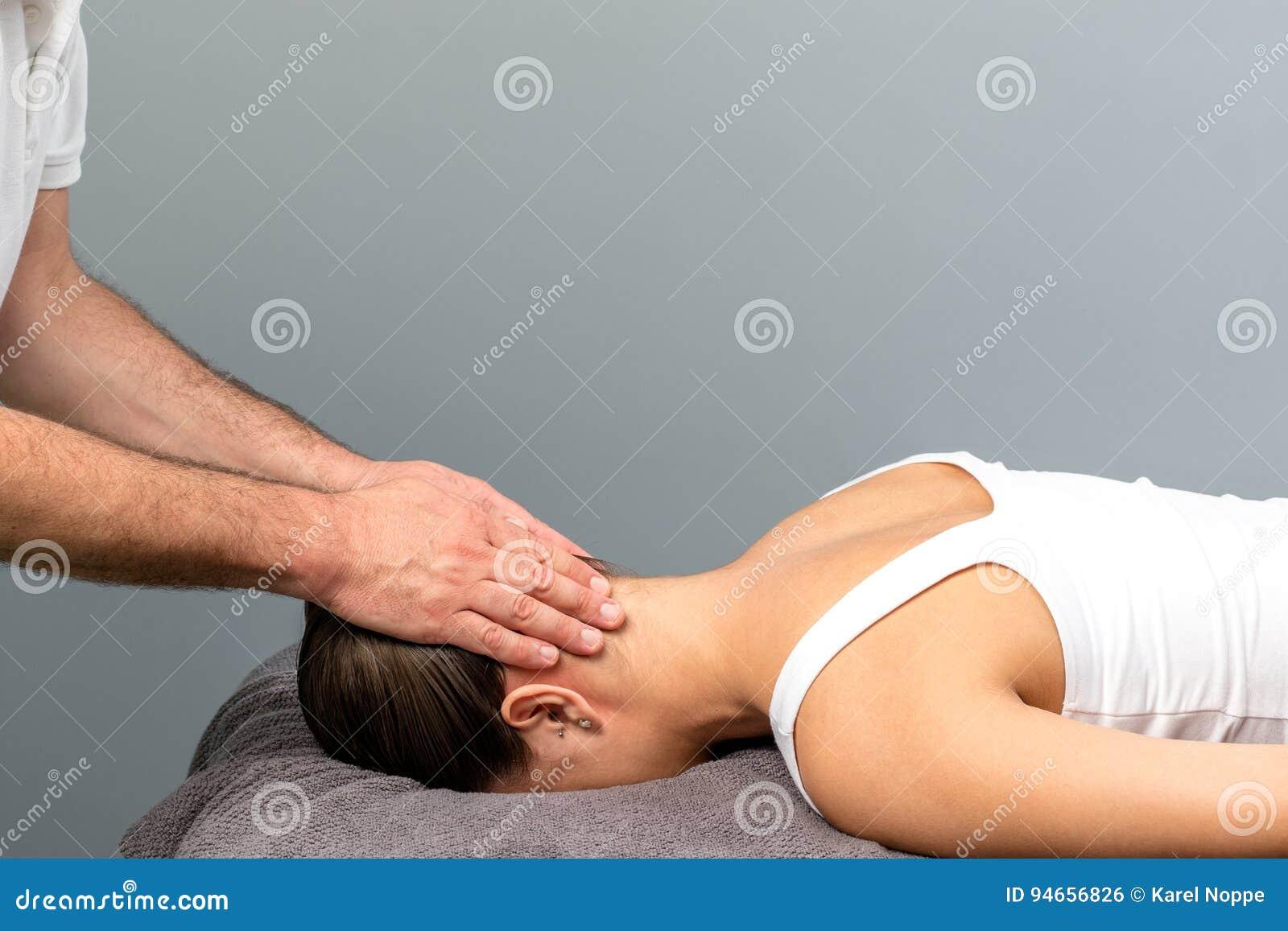 Therapist Applying Pressure On Back Of Female Head  Stock