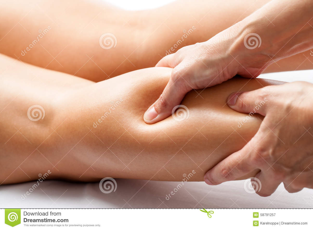 Therapist applying pressure with thumb on female calf muscle.