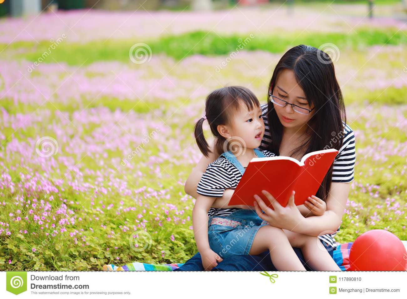 Happy Little Cute Baby Girl Smile And Read Book With Mother