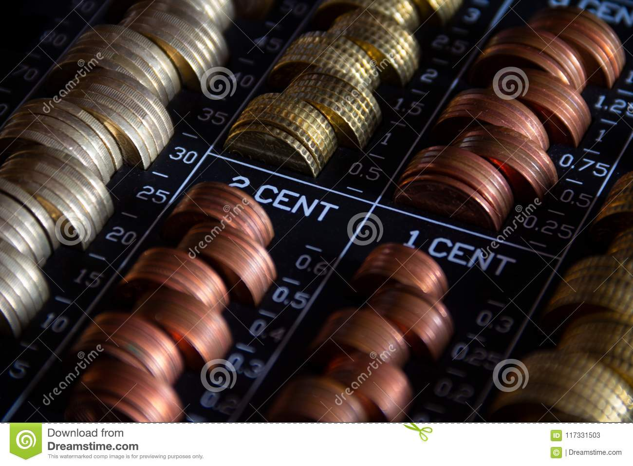 Stacked coins in a metallic cash box with a lock