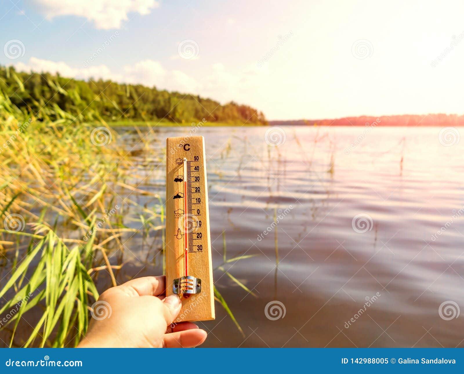 Thermometer die 30 graden van Celsius tonen van hitte tegen de achtergrond van het meerwater en de blauwe hemel in zonlicht