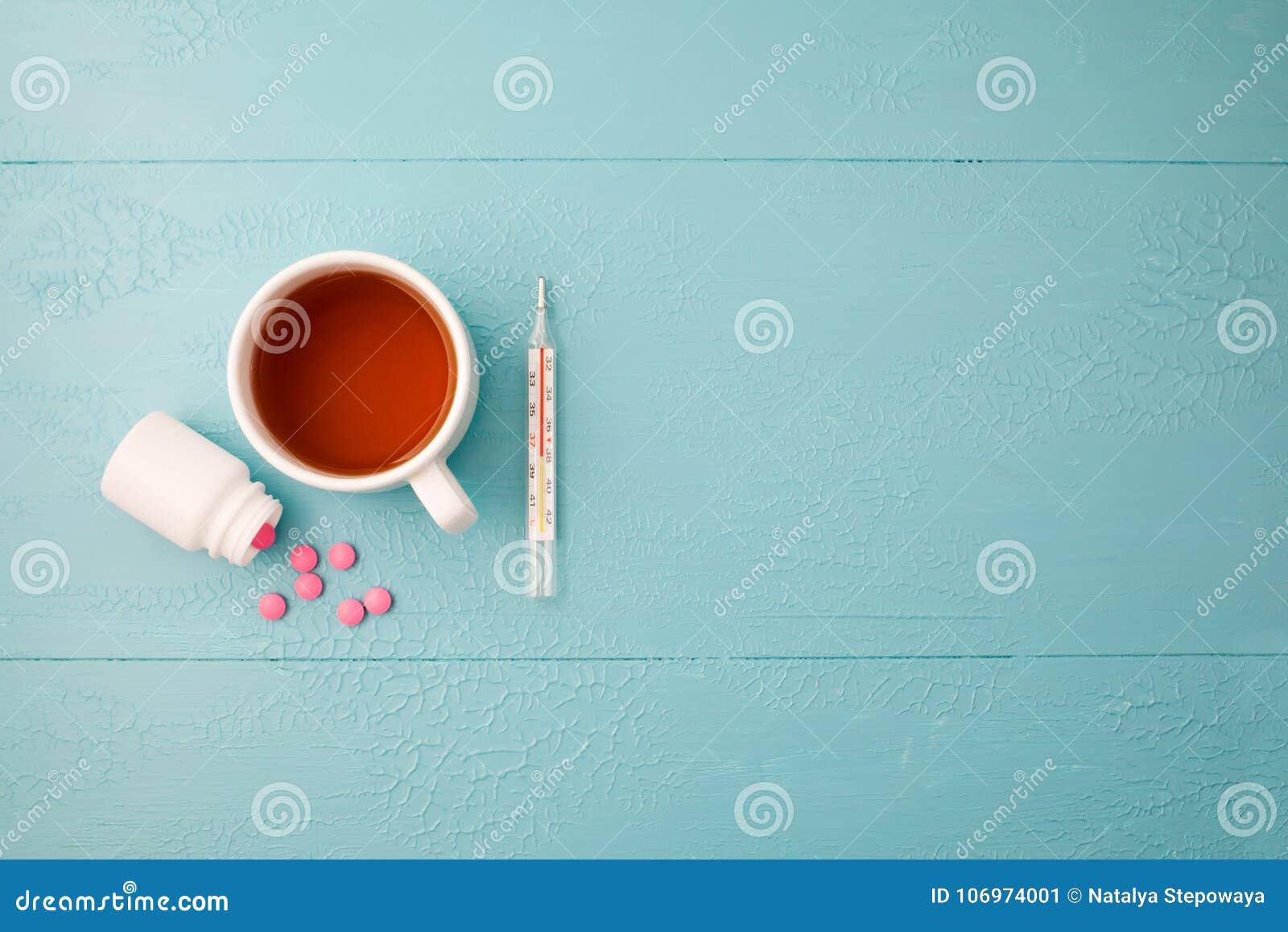 Thermometer, tabletten en thee op een blauwe achtergrond Ruimte voor tekst Hoogste mening