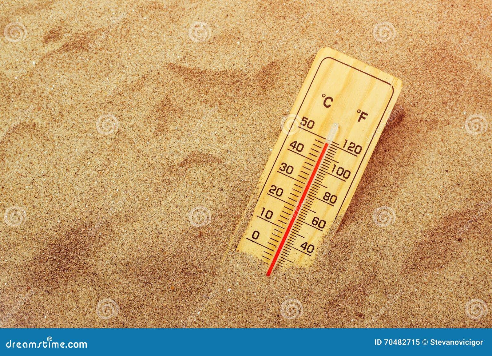 Thermometer on warm desert sand
