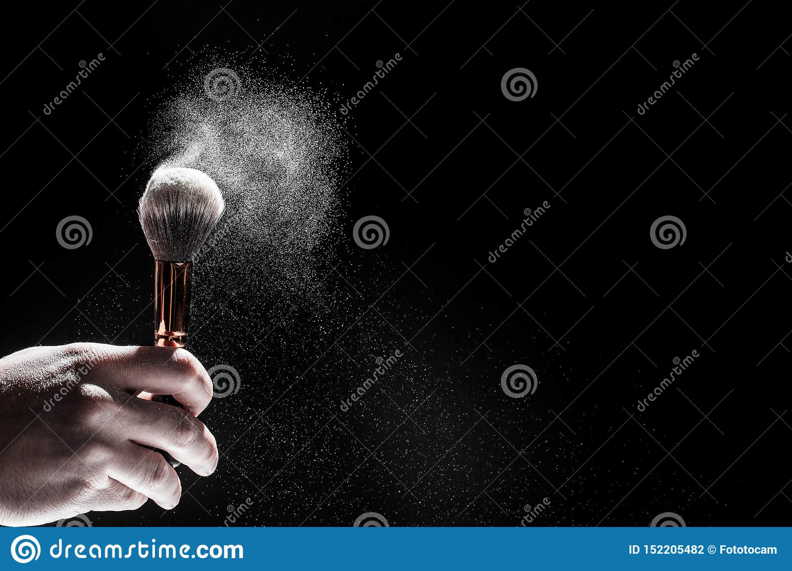 Thick black brush in motion and loose powder particles scattered around