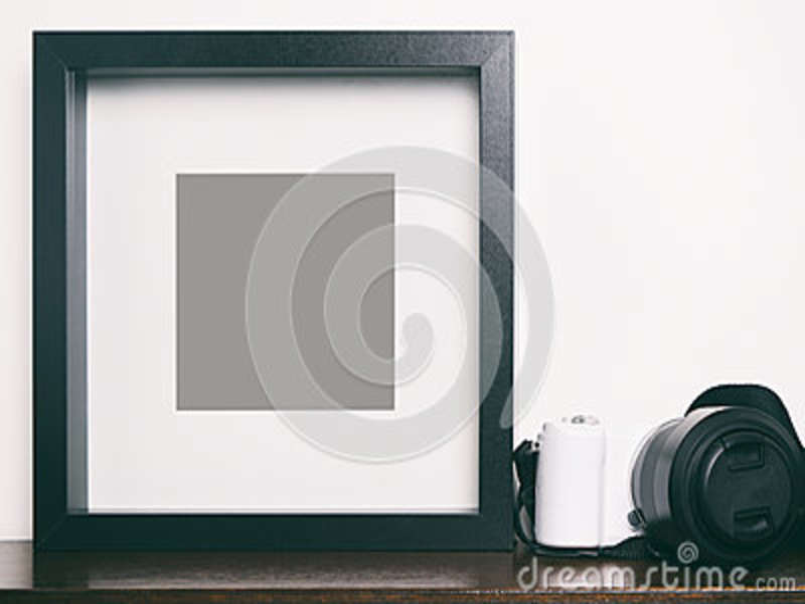 Thick blank black photo frame on shelf with camera