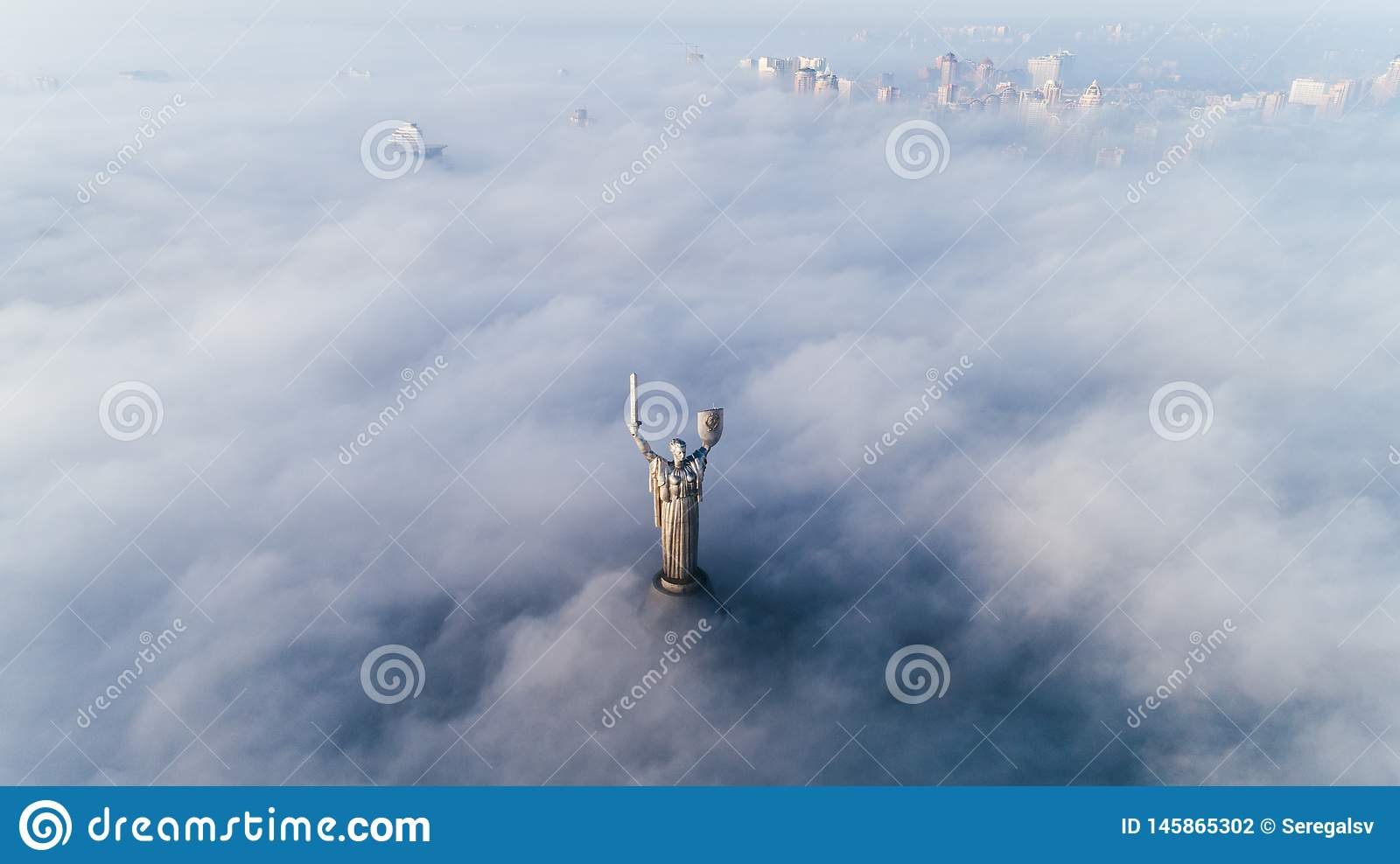 Thick clouds of autumn fog and the Motherland monument sticking out of them
