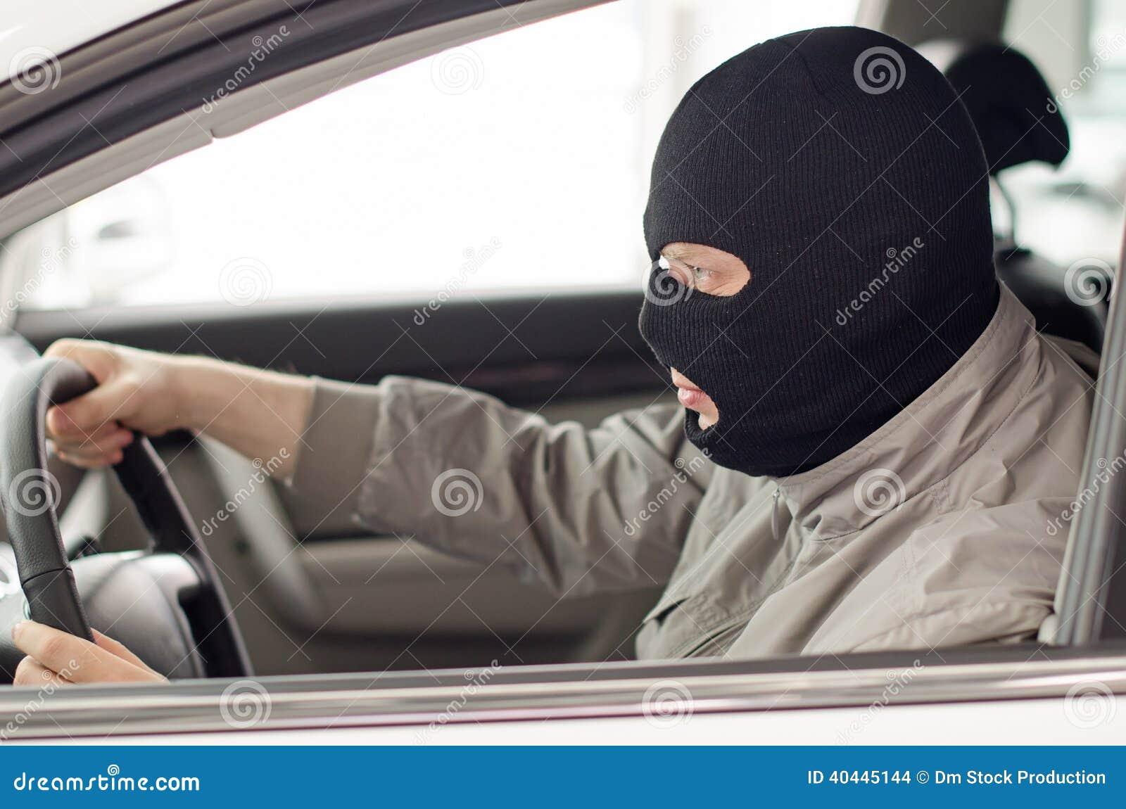 Thief in mask steals car.