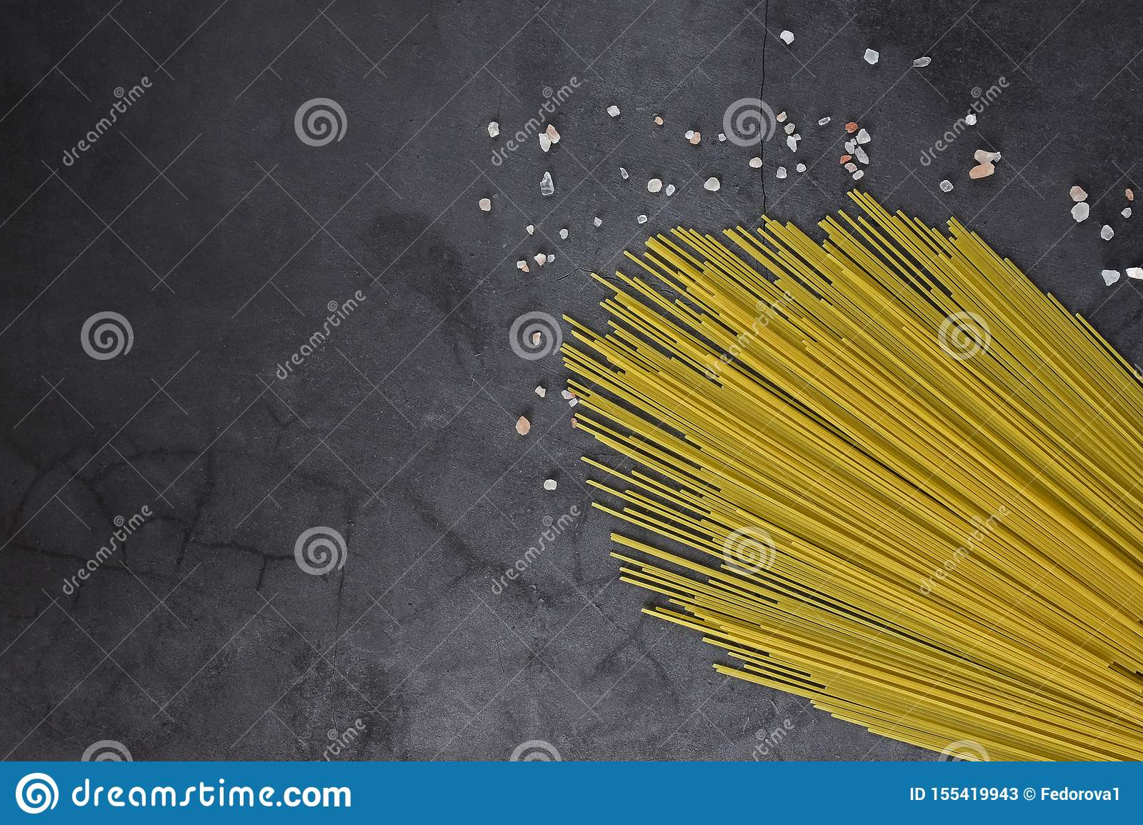 Thin threads of pasta on a neutral gray background