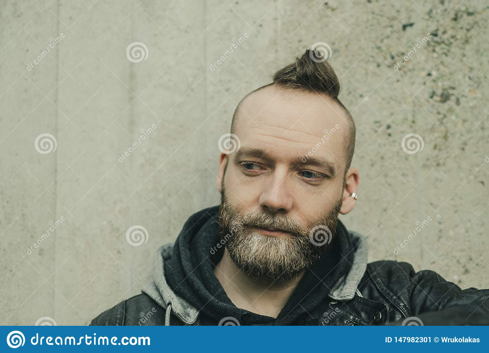 A man with mohawk is looking down in front of the camera