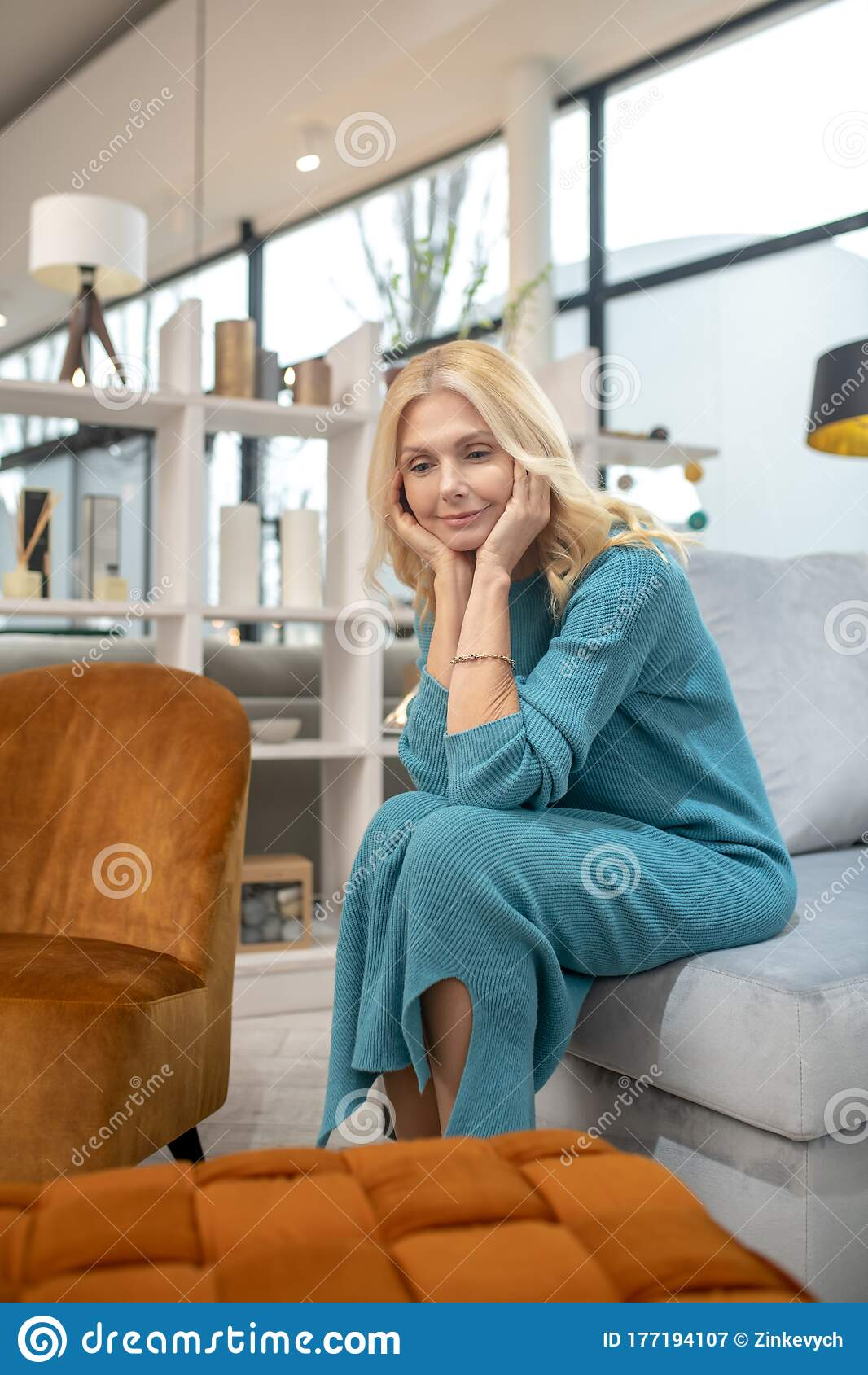Picture of: Blonde Woman In A Blue Dress Sitting On A Sofa Stock Image Image Of Female Store 177194107