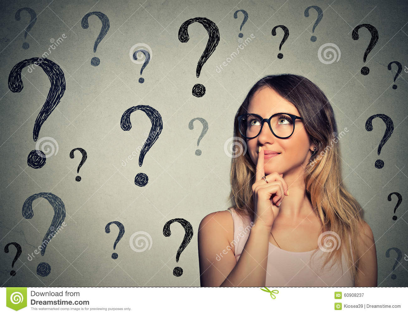 Thinking business woman with glasses looking up at many questions mark