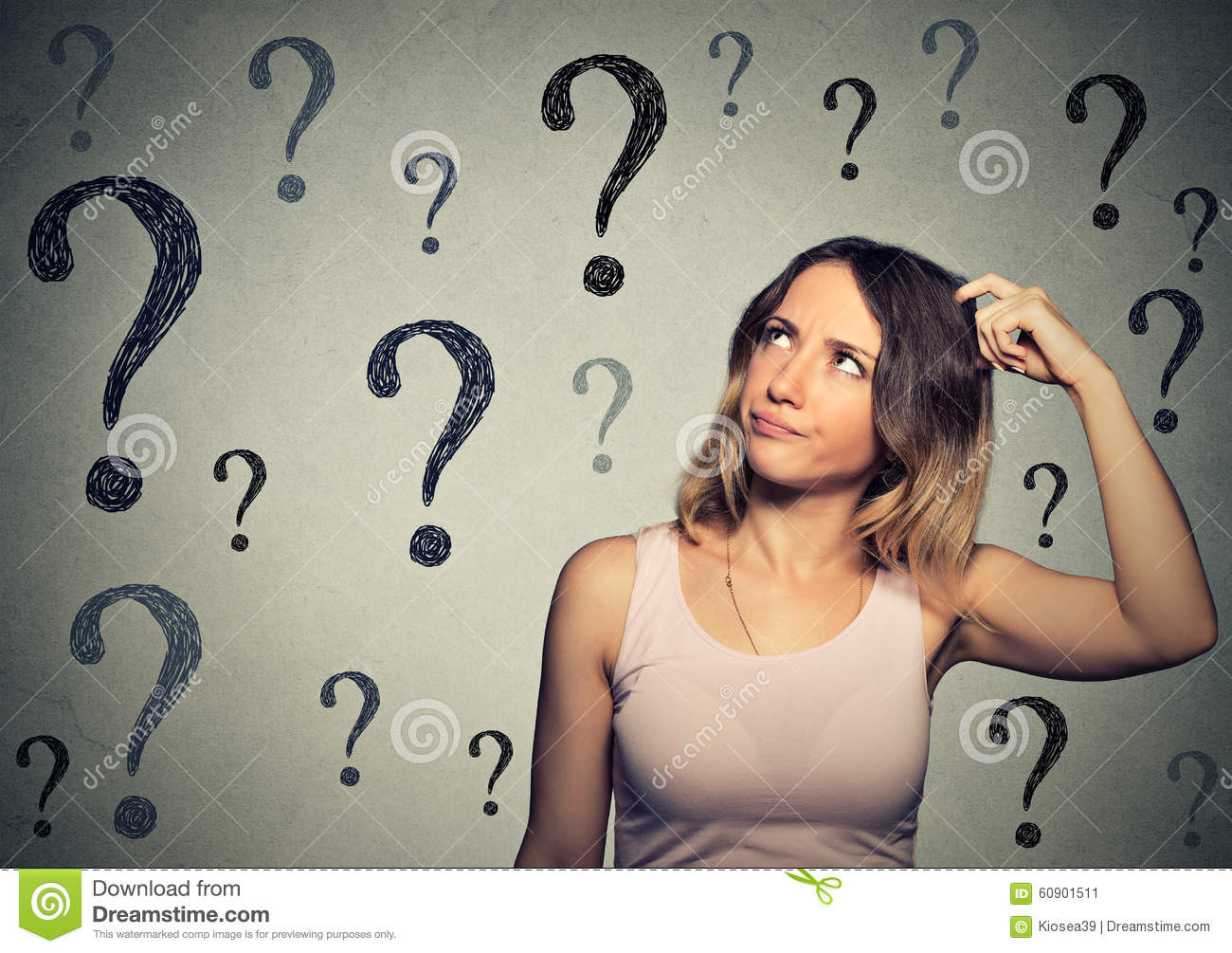 Thinking woman looking up at many questions marks
