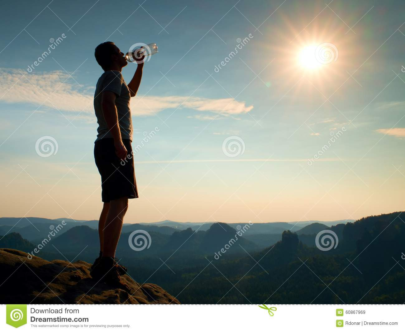 Thirsty Hiker In Black Pants Drinks From Bottle Of Water