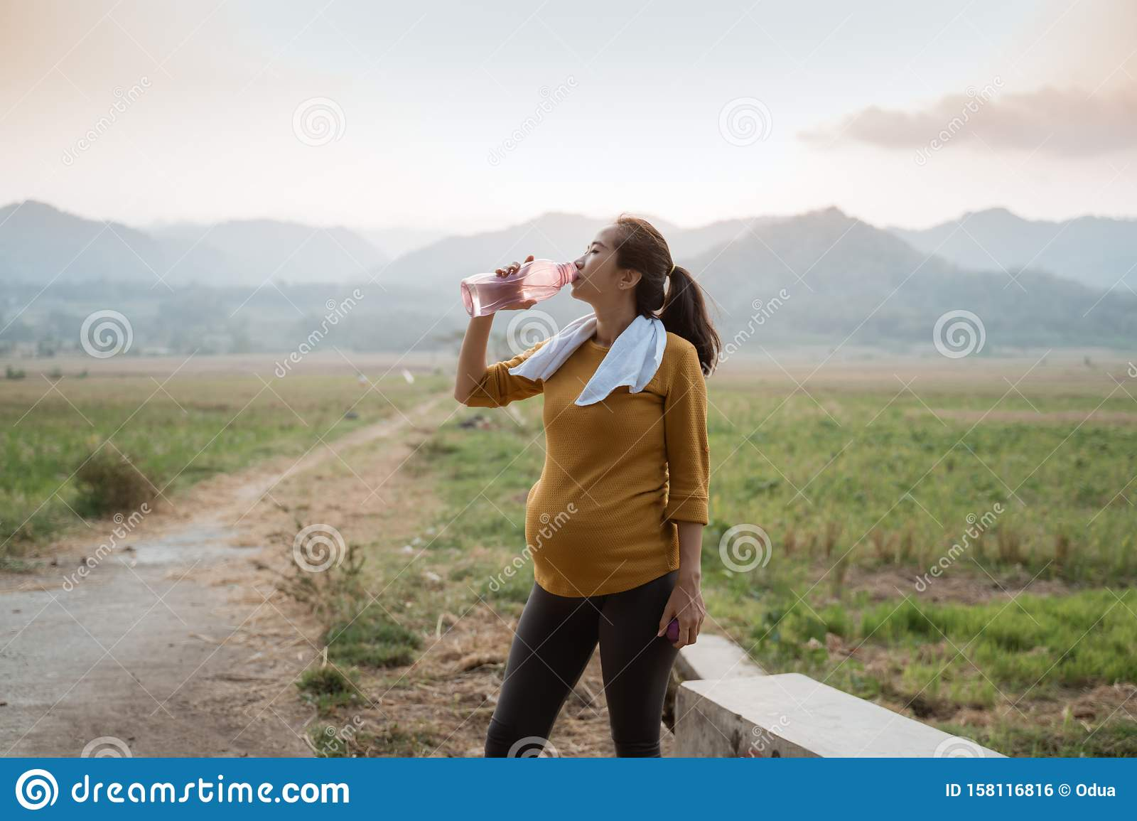 Pregnant Woman After Workout Drinking A Bottle Of Water Stock