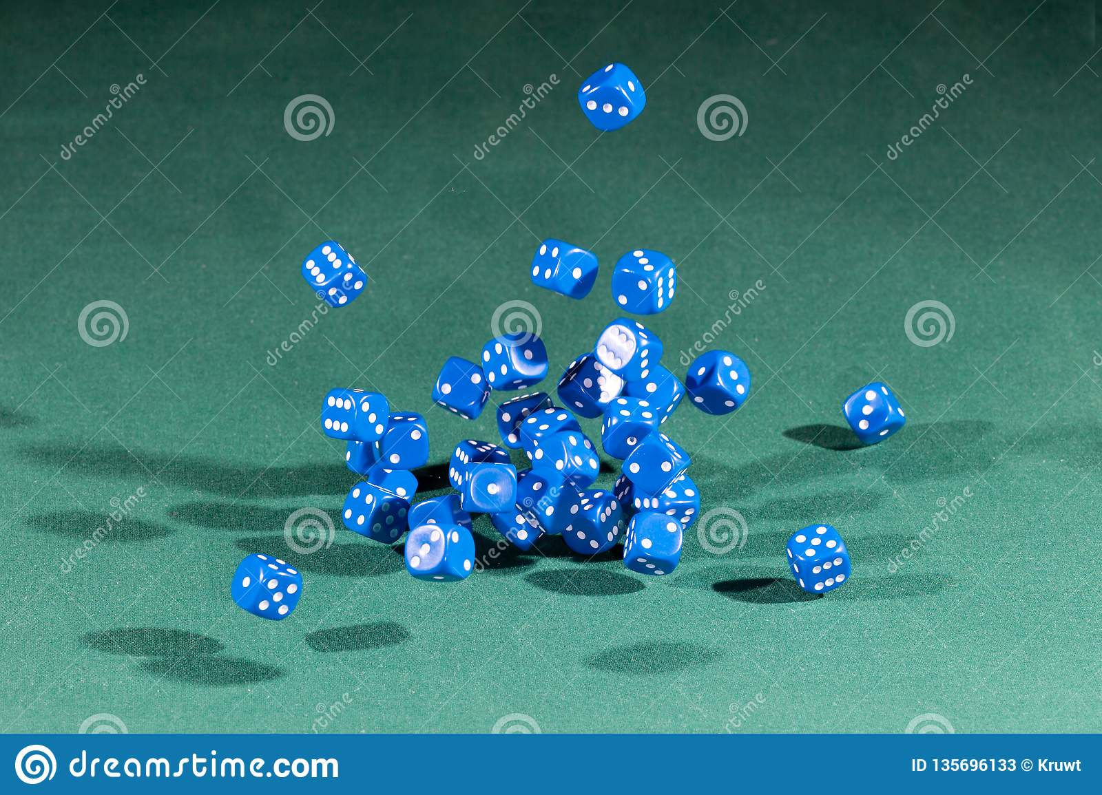 Thirty blue dices falling on a green table