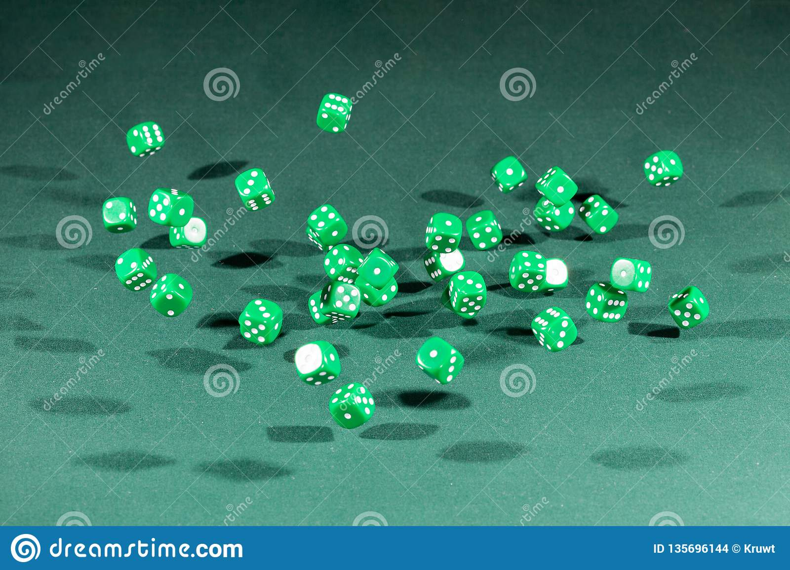 Thirty green dices falling on a green table