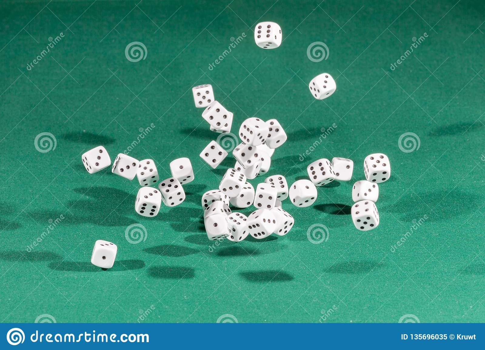 Thirty white dices falling on a green table