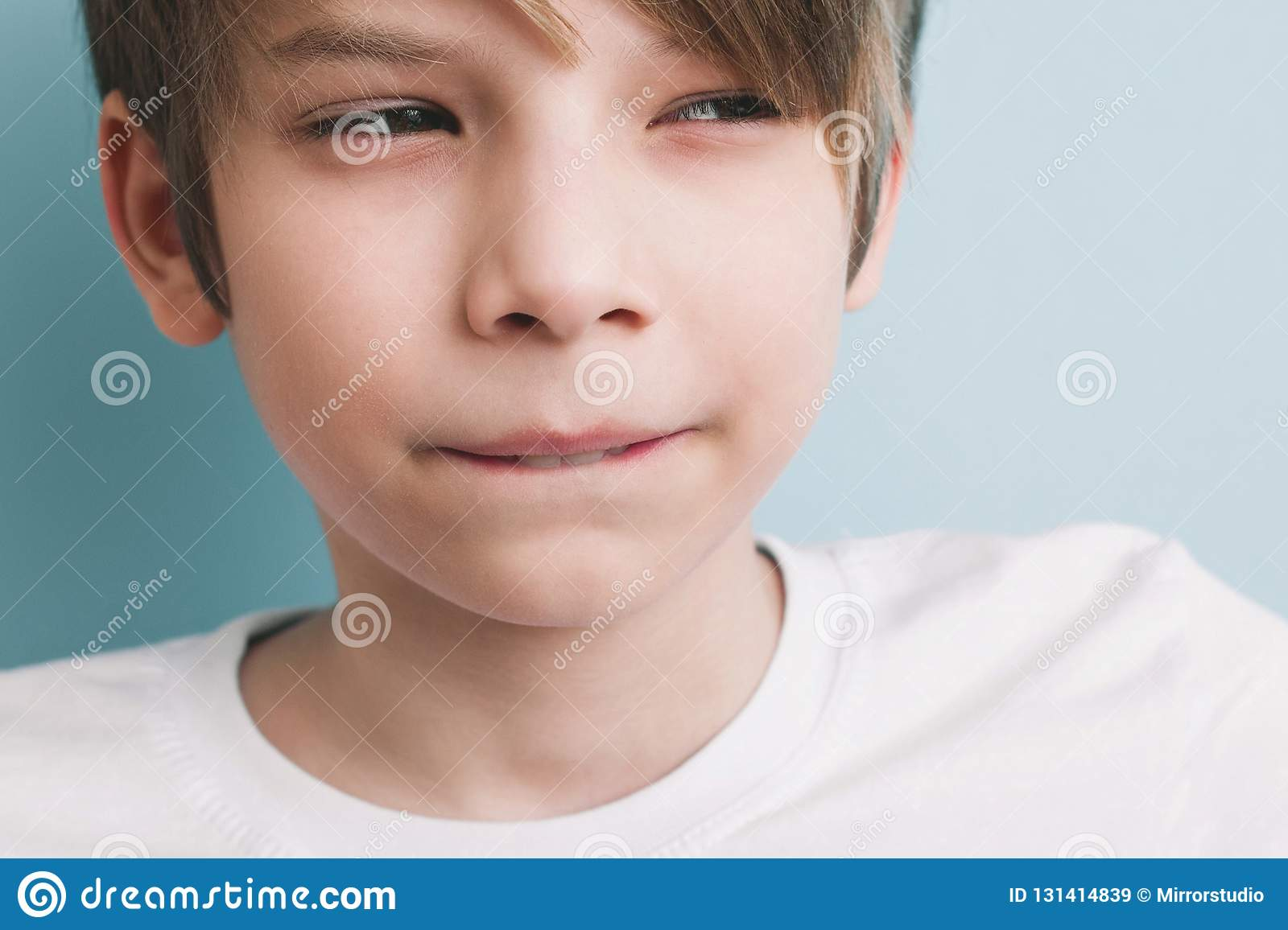 Thoughtful boy with bitter prank bitten his lower lip with his teeth and narrowed his eyes
