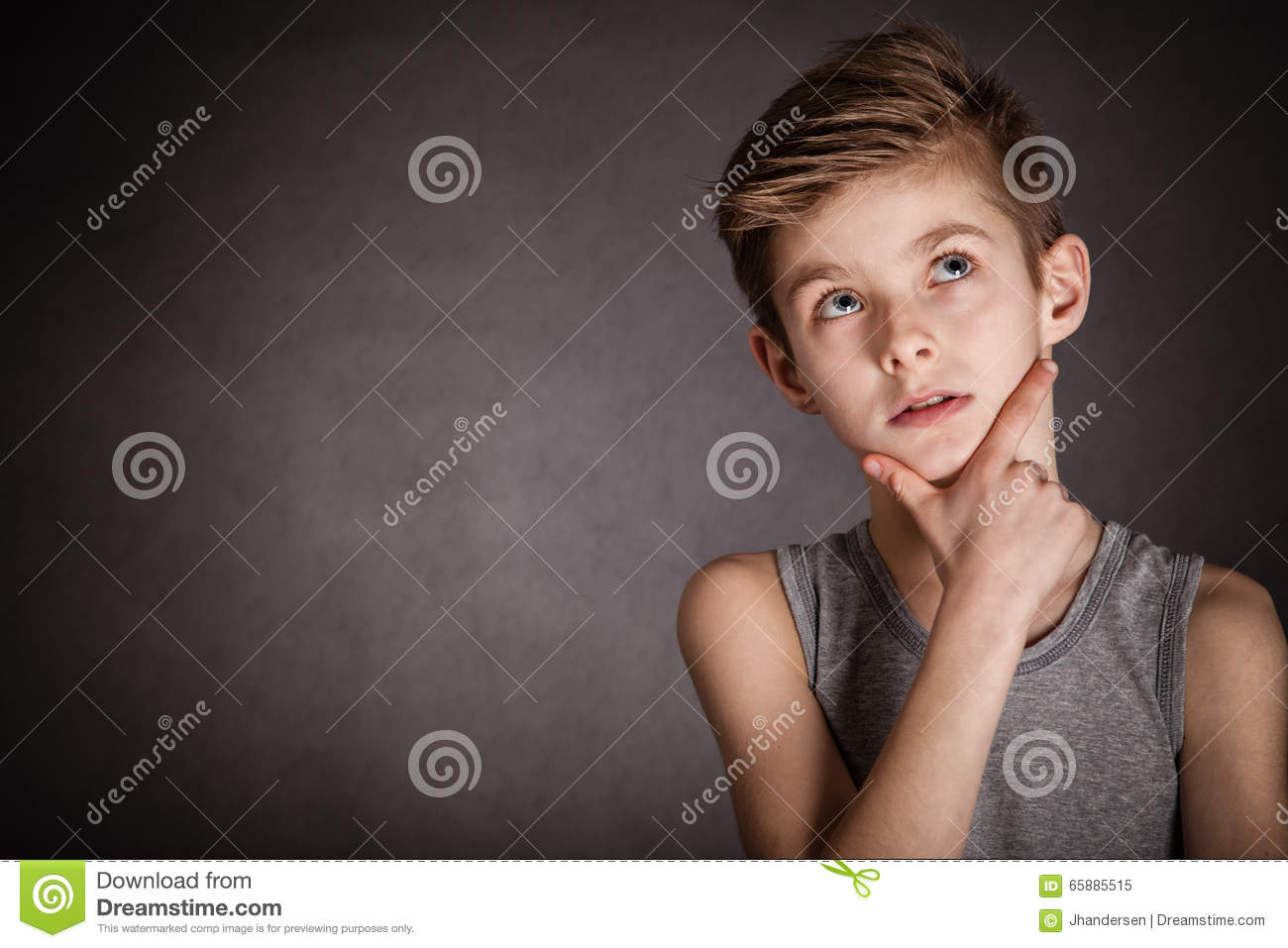 Thoughtful Boy Looking Up on Gray with Copy Space