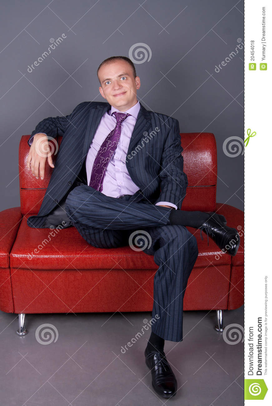 Thoughtful Guy In A Suit Sitting On A Red Couch Stock