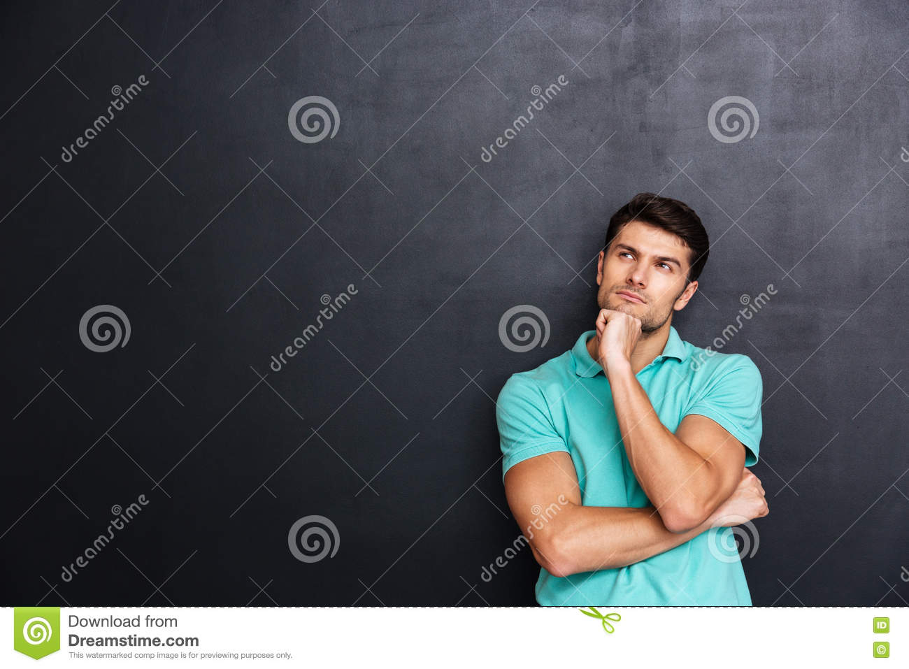 Thoughtful handsome young man standing and thinking