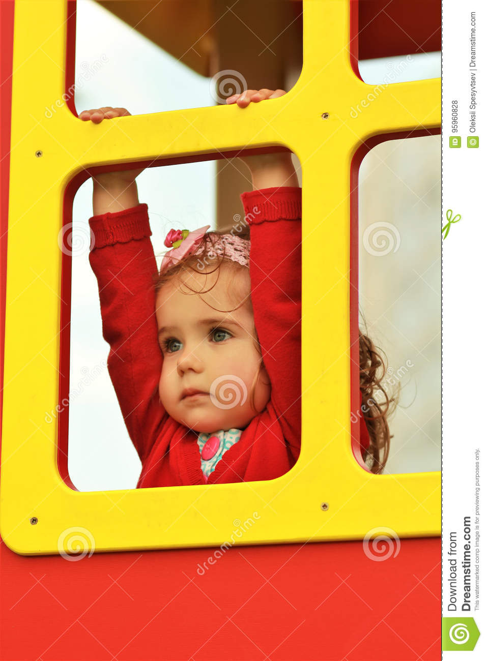 Thoughtful little girl in red looking in the distance out of a window of a colorful wooden house
